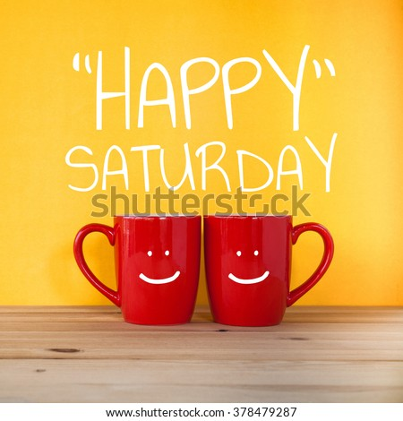 Happy saturday word.Two cups of coffee and stand together to be heart shape on yellow background with smile face on cup. - stock photo
