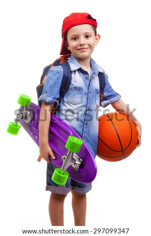 Happy school boy holding a skateboard and a basketball on white background - stock photo