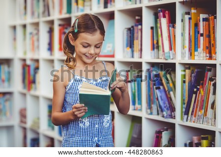 Happy school girl reading a book in library at school - stock photo