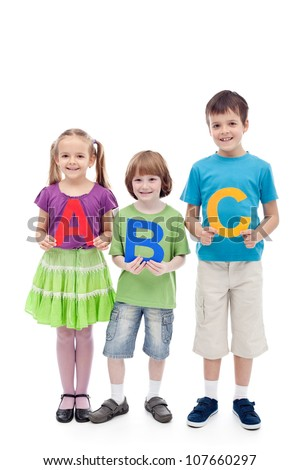Happy school kids holding large abc letters - learning concept, isolated - stock photo