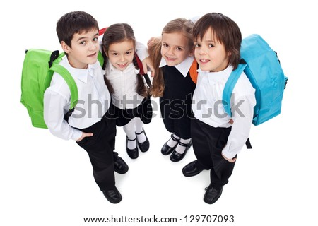Happy school kids with back packs - holding each other, looking up - isolated - stock photo