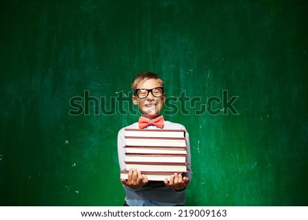 Happy schoolboy in eyeglasses holding stack of books while standing by the blackboard and looking at camera - stock photo