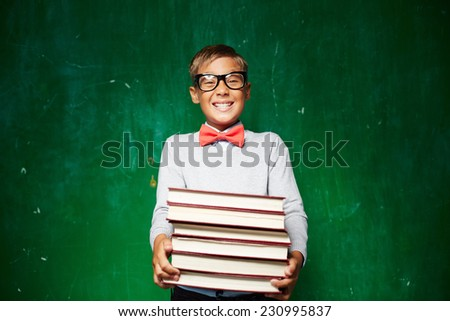 Happy schoolboy in smart casual holding stack of books - stock photo