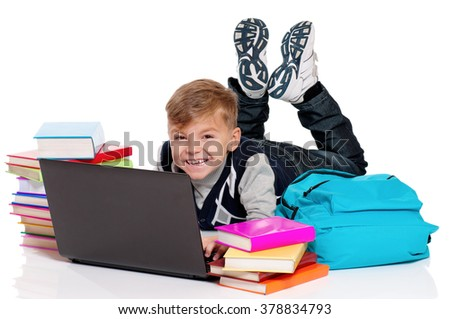 Happy schoolboy lying on floor with laptop, backpack and books isolated on white background - stock photo