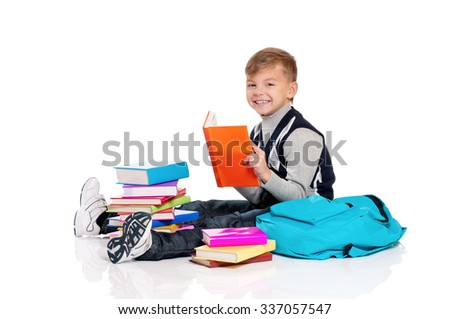 Happy schoolboy sitting on floor with backpack and books isolated on white background - stock photo