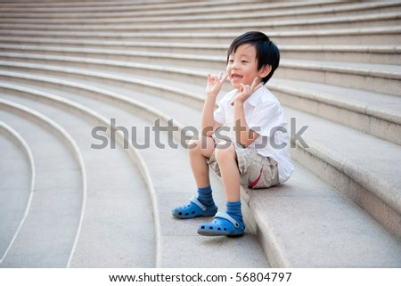 Happy schoolboy sitting on the stairs - stock photo