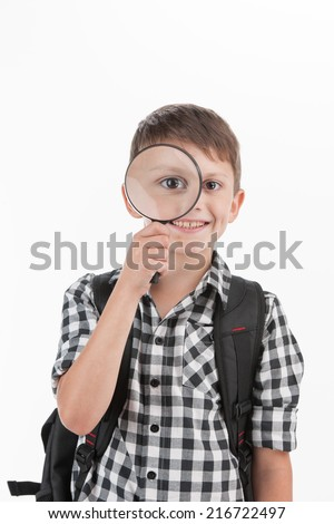 Happy schoolboy wearing backpack and holding magnifying lens. cute schoolboy walking isolated on white background - stock photo