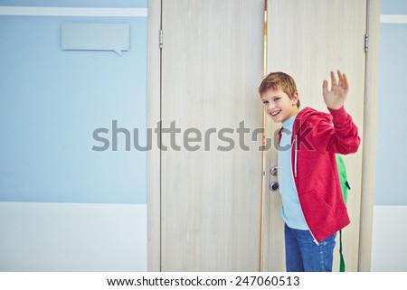 Happy schoolboy with backpack opening classroom door and waving his hand - stock photo