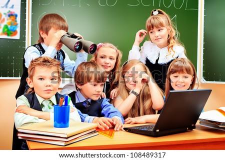 Happy schoolchildren at a classroom looking through binoculars. Education. - stock photo