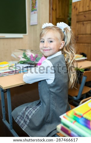 Happy schoolgirl in school uniform turning back while sitting at classroom - stock photo
