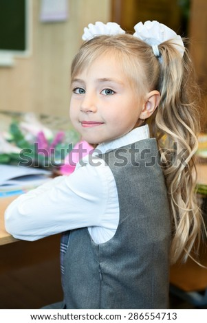 Happy schoolgirl in uniform turning back while sitting at the school desk - stock photo