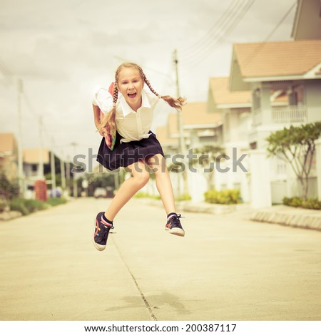 happy schoolgirl jumping near the house at the day time and ready to go to school - stock photo