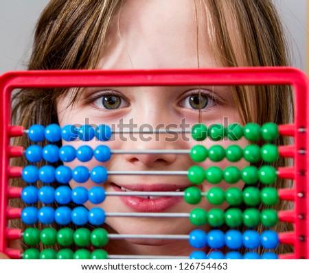 Happy schoolgirl learning mathematics using abacus - stock photo