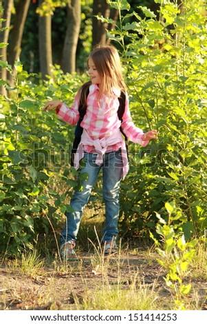Happy Schoolgirl Outdoor/Smiling little schoolgirl with a backpack walking home from school - stock photo