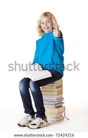 Happy schoolgirl sitting on school books showing thumb up. Isolated on white background. - stock photo