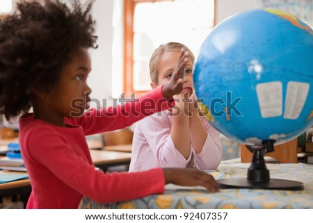 Happy schoolgirls looking at a globe in a classroom - stock photo