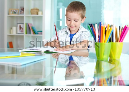 Happy schoolkid drawing with multicolored pencils - stock photo