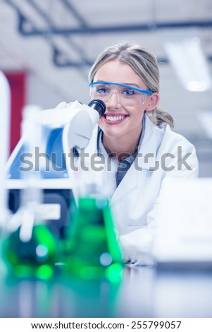 Happy science student working with microscope in the lab at the university - stock photo
