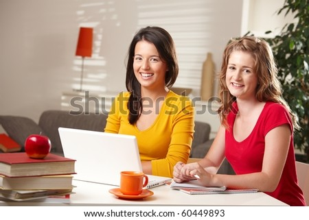 Happy seen students smiling at camera with laptop computer on table at home. - stock photo