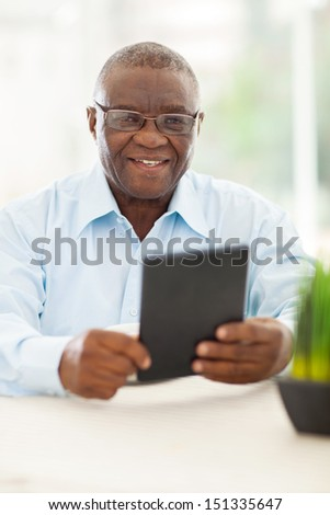 happy senior african man holding tablet computer at home - stock photo