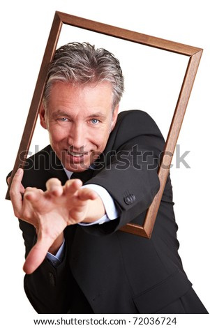 Happy senior business man reaching with hand through empty frame - stock photo