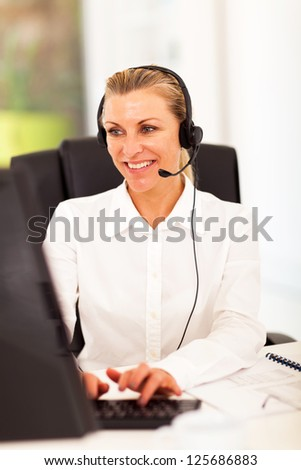 happy senior businesswoman with headphones in front of computer - stock photo