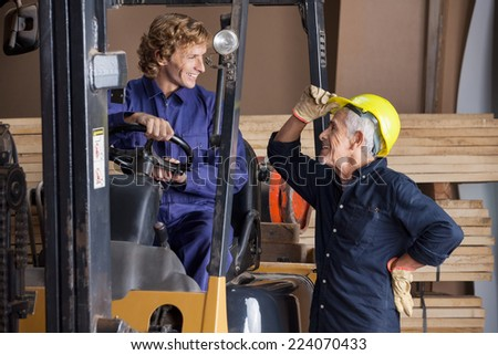 Happy senior carpenter communicating with colleague using forklift in workshop - stock photo
