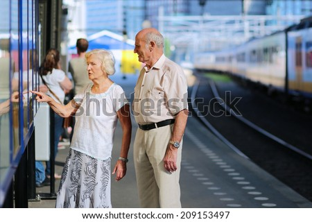 Happy senior caucasian couple travelling around Europe waiting for train in railway station platform in Amsterdam - active retirement concept  - stock photo