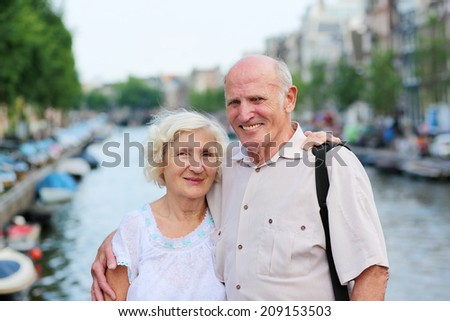 Happy senior caucasian couple travelling around Europe walking in the streets of Amsterdam, enjoying scenes of the canals on a sunny summer day - active retirement concept  - stock photo