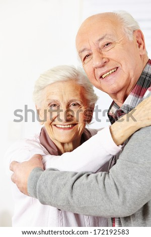 Happy senior citizen couple dancing together and smiling - stock photo