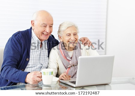 Happy senior citizen couple using laptop computer at home - stock photo