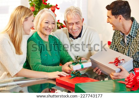 Happy senior citizens celebrating christmas with their children and gifts - stock photo