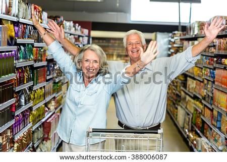 Happy senior couple at the supermarket raising arms - stock photo