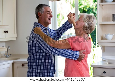 Happy senior couple dancing in kitchen at home - stock photo