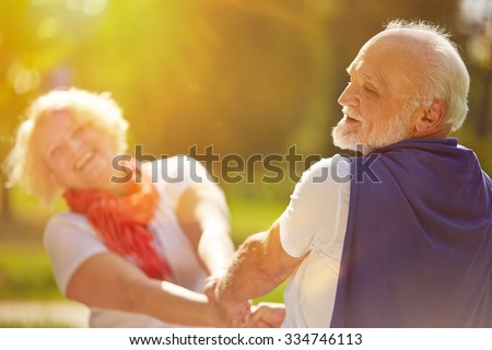 Happy senior couple dancing in the sun in summer in nature - stock photo