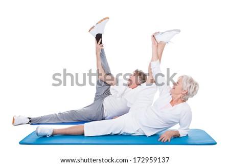 Happy Senior Couple Doing Exercise On Blue Exercise Mat - stock photo