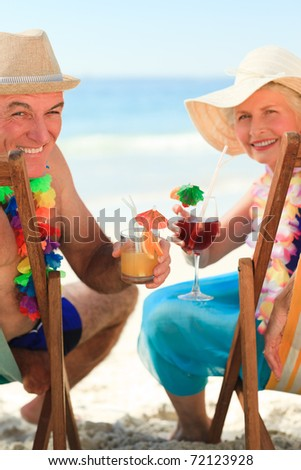Happy senior couple drinking a cocktail - stock photo