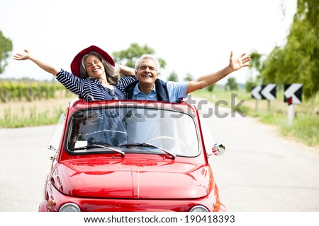 Happy senior couple driving vintage car - stock photo
