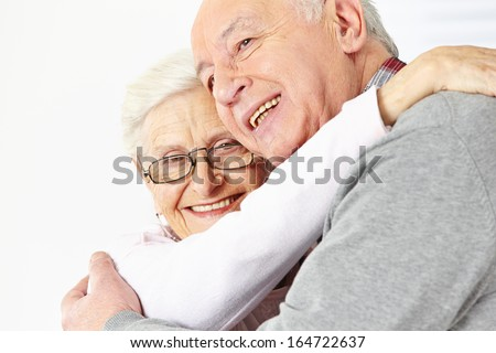 Happy senior couple embracing each other and smiling - stock photo