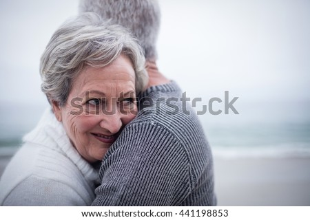 Happy senior couple embracing each other on the beach - stock photo