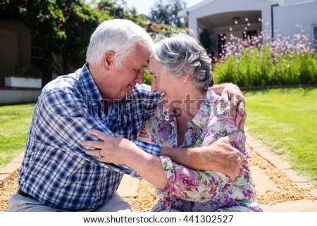 Happy senior couple embracing in the garden - stock photo