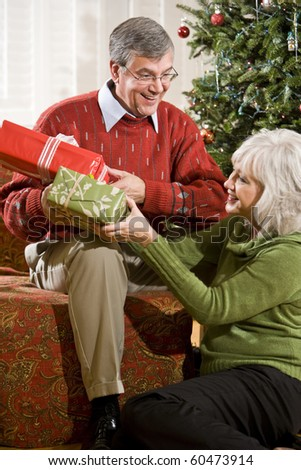 Happy senior couple exchanging Christmas gifts at home by tree - stock photo