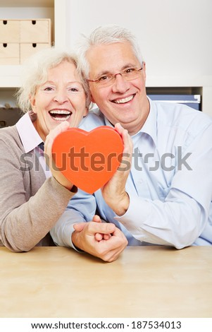 Happy senior couple holding a red big heart - stock photo