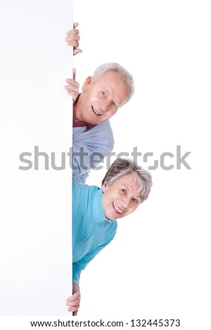 Happy Senior Couple Holding Blank Placard On White Background - stock photo