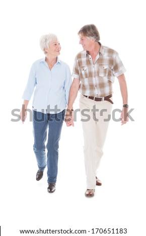 Happy Senior Couple Holding Hand And Walking Over White Background - stock photo
