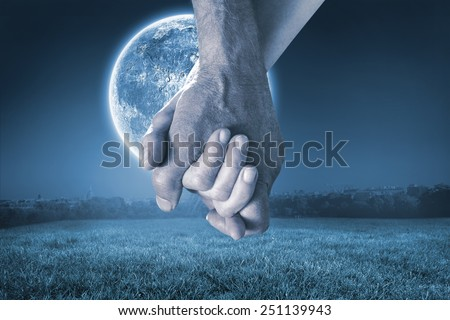 Happy senior couple holding hands against large moon over paris - stock photo