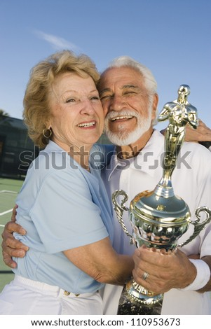 Happy senior couple holding trophy after winning - stock photo