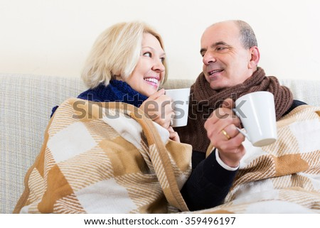 Happy senior couple in woolen scarf warming up with hot tea - stock photo