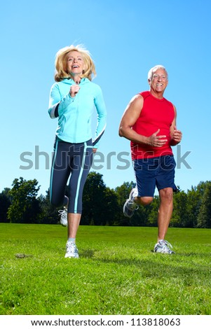 Happy senior couple jogging in the park. - stock photo