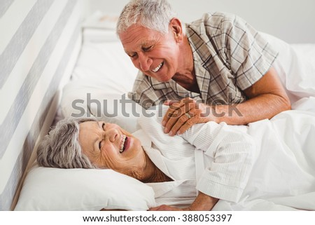 Happy senior couple laughing on bed in bedroom - stock photo